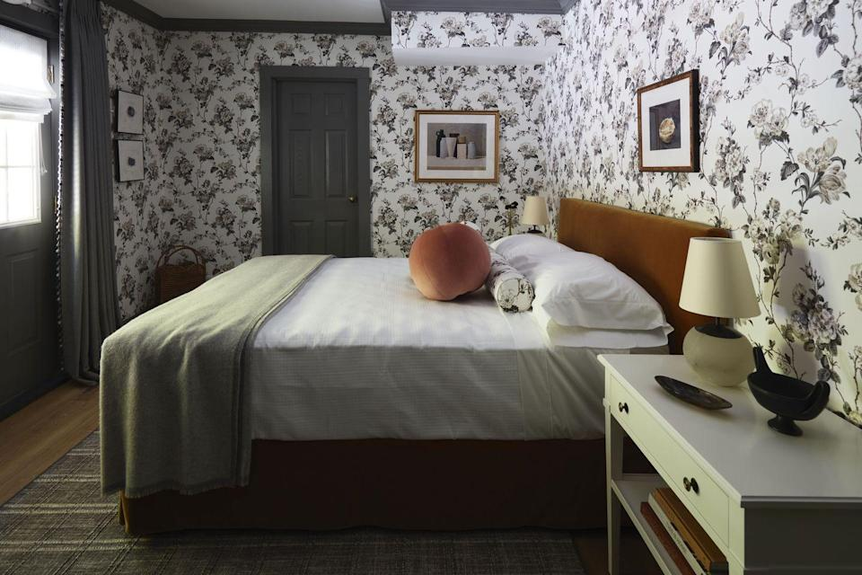 """<p>Shawna Underwood's bedroom is a fresh take on a quaint New England aesthetic. She wanted to make guests feel right at home with inviting textures, whimsical details, and a neutral floral wallpaper by <a href=""""https://fschumacher.com/"""" rel=""""nofollow noopener"""" target=""""_blank"""" data-ylk=""""slk:Schumacher"""" class=""""link rapid-noclick-resp"""">Schumacher</a>, but she also took creative license with shape, scale, and color. Underwood was thrilled to partake in the inn's transformation: """"The showhouse brings comfort in knowing it is OK to have a design perspective that represents your background, culture, or interpretation of the world around you,"""" she said. </p>"""