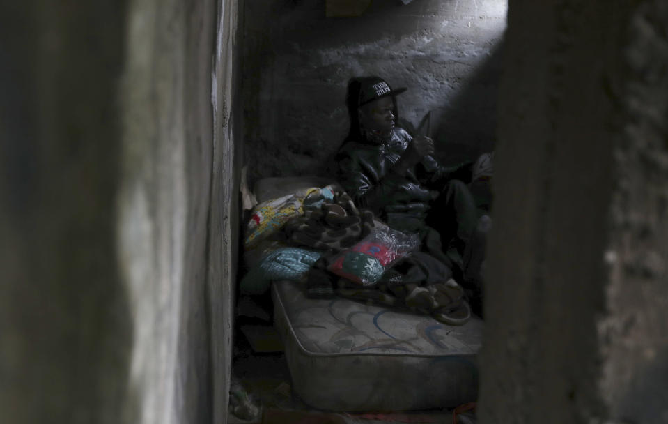 A homeless person sits inside an abandoned building in Quito, Ecuador, Thursday, March 18, 2021, amid the new coronavirus pandemic. (AP Photo/Dolores Ochoa)