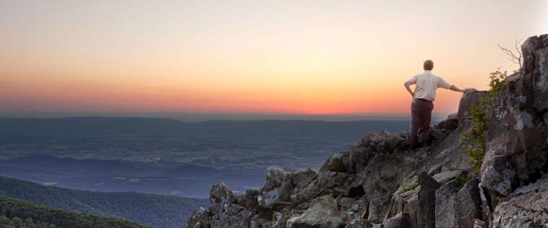 Back view of man watching sunset from rocky summit of Stony Man on Skyline Drive in Virginia