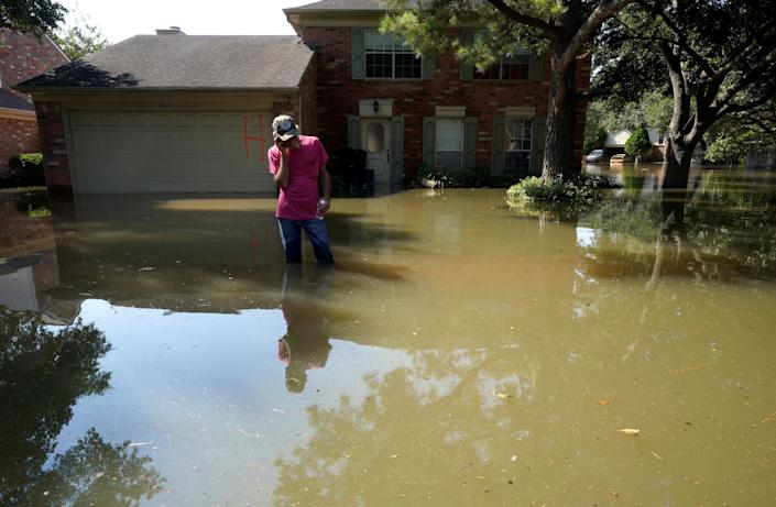 Carl Ellis talks to his daughter stuck in Canada, while standing in front of her house surrounded by Harvey floodwaters on Aug. 31.