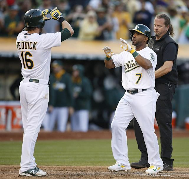 Oakland Athletics' Alberto Callaspo (7) is congratulated by Josh Reddick (16) after Alberto Callaspo hit a 2-run home run in the seventh inning against the Los Angeles Angels of a baseball game Sunday, Aug. 24, 2014, in Oakland, Calif. (AP Photo/Tony Avelar)