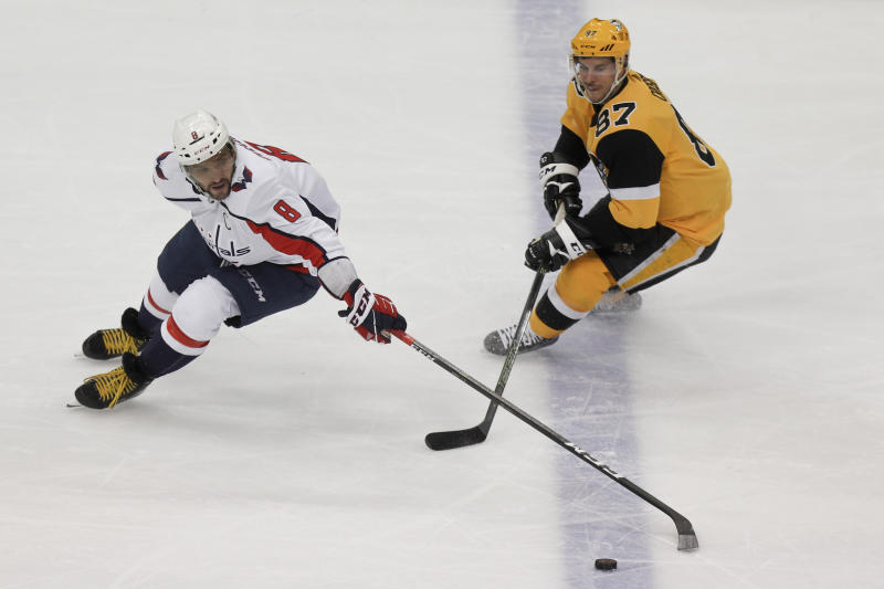 Pittsburgh Penguins' Brian Dumoulin (8) controls the puck in front of Pittsburgh Penguins' Sidney Crosby (87) during the first period of an NHL hockey game, Saturday, March 7, 2020, in Pittsburgh. (AP Photo/Keith Srakocic)