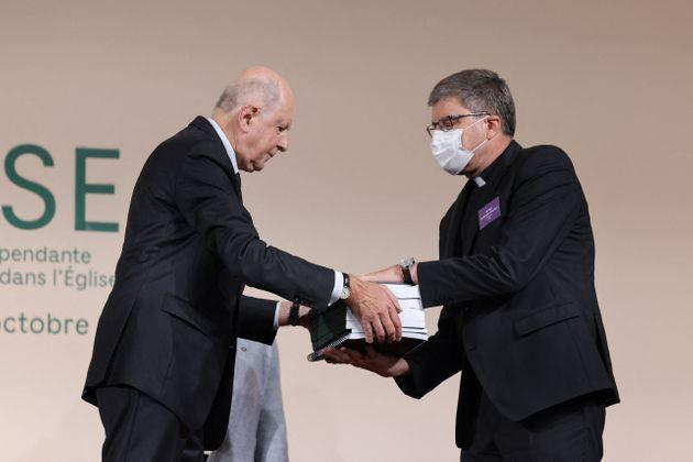 Commission president Jean-Marc Sauve (L), hands copies of the report to Catholic Bishop Eric de Moulins-Beaufort, president of the Bishops' Conference of France (CEF), during the publishing of a report by an independant commission into sexual abuse by church officials (Ciase) on October 5, 2021, in Paris. - An independent inquiry into alleged sex abuse of minors by French Catholic priests, deacons and other clergy has found some 216,000 victims of paedophilia from 1950 to 2020, a