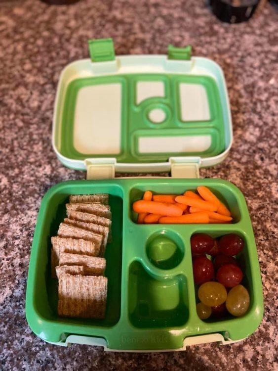 bento box with carrots, crackers and grapes