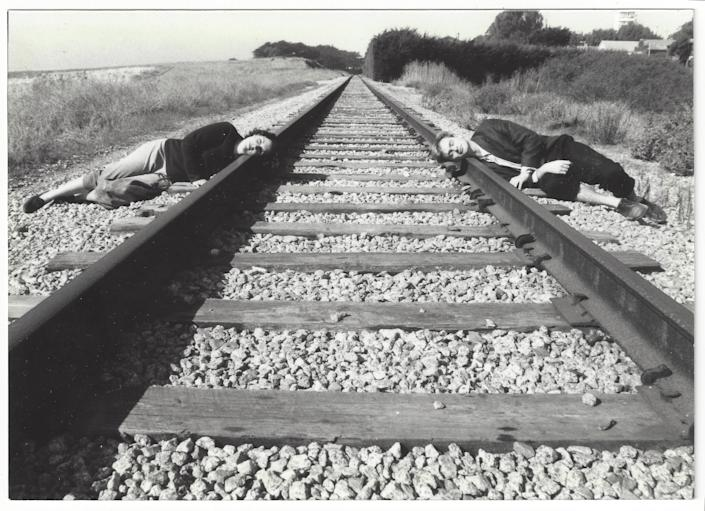 Christopher Nolan and Emma Thomas lying on train tracks during a vacation in California.
