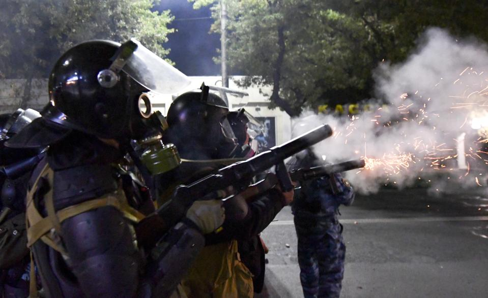 Riot police disperse protesters during a rally against the results of a parliamentary vote in Bishkek, Kyrgyzstan, Monday, Oct. 5, 2020. Large crowds of people have gathered in the center of Kyrgyzstan's capital to protest against the results of a parliamentary election, early results of which gave the majority of seats to two parties with ties to the ruling elites amid allegations of vote buying. (AP Photo/Vladimir Voronin)