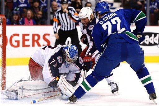 Vancouver Canucks' Daniel Sedin battles for the puck in front of Columbus Blue Jackets goalie Sergei Bobrovsky and forward Vinny Prospal during the first period of an NHL hockey game in Vancouver, British Columbia, Tuesday, March 26, 2013. (AP Photo/The Canadian Press, Jonathan Hayward)
