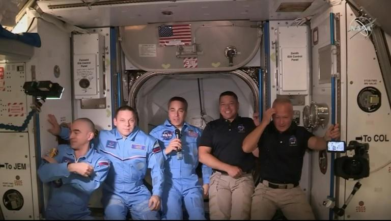 Douglas Hurley (R) and Robert Behnken (2ndR) arrive at the International Space Station, to be greeted by other astronauts