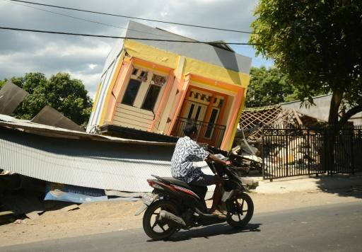 A man riding a motorcycle passes by a damaged house at Sira village in northern Lombok