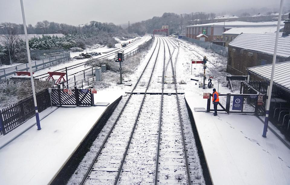 A rail worker at Hexham train station, Northumberland. Heavy snow and freezing rain is set to batter the UK this week, with warnings issued over potential power cuts and travel delays. (Photo by Owen Humphreys/PA Images via Getty Images)