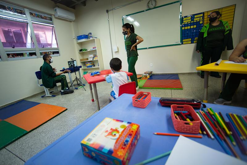 BRASILIA, BRAZIL - AUGUST 06: A teacher speaks to his class face-to-face and remotely simultaneity during first day back to school amidst the coronavirus (COVID-19)pandemic at the Arvense School on August 06, 2020 in Brasilia. The school has taken measures to prevent Covid-19 such as reducing students per class, intensifying cleaning, disinfection booths and measuring body temperature when entering and leaving students and staff. The government of the Federal District has already authorized the resumption of classes in private schools, but in public schools they are expected to reopen at the end of August. Brazil has over 2.912,000 confirmed positive cases of Coronavirus and has over 98,493 deaths. (Photo by Andressa Anholete/Getty Images)
