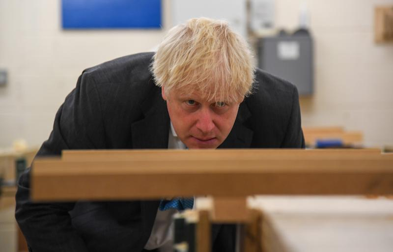 Prime Minister Boris Johnson looks at a piece of wood in a vice during a visit to Exeter College. The visit comes ahead of a speech in which he is expected to announce guaranteed opportunities for life-long learning to help create a jobs recovery after the pandemic.