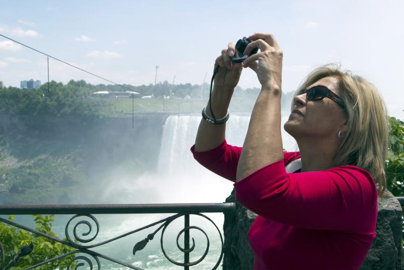 Bogumila Zbyszewska of Toronto photographs the tightrope that Nik Wallenda will use hangs over Niagara Falls in Niagara Falls, Ontario, Canada., on Friday, June 15, 2012. Conditions appear good leading up to the nationally televised stunt scheduled for Friday night. When Wallenda leaves terra firm about 10:15, it should be in the low 60s with winds under 10 mph from the east, roughly at his back. (AP Photo/The Canadian Press, Frank Gunn)