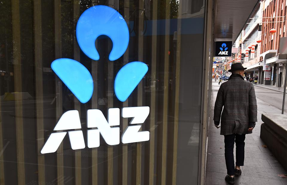 A man walks past an ANZ bank sign in Melbourne's Chinatown on April 30, 2020. - Australia's ANZ Bank announced a 50-percent dive in after-tax profits, as the lender set aside one billion Australia dollars (655 million US) to cover expected losses resulting from the coronavirus fallout. (Photo by William WEST / AFP) (Photo by WILLIAM WEST/AFP via Getty Images)
