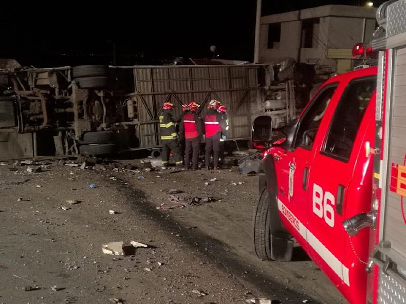 Firefighters and rescuers work next to the undercarriage of a bus that crashed and flipped east of the Ecuadoran capital killing at least 23 people in this