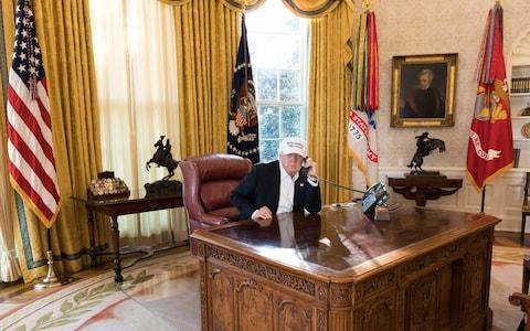 President Donald Trump talks on the phone in the Oval Office during negotiations to end the Democrats government shutdown - Credit: White House