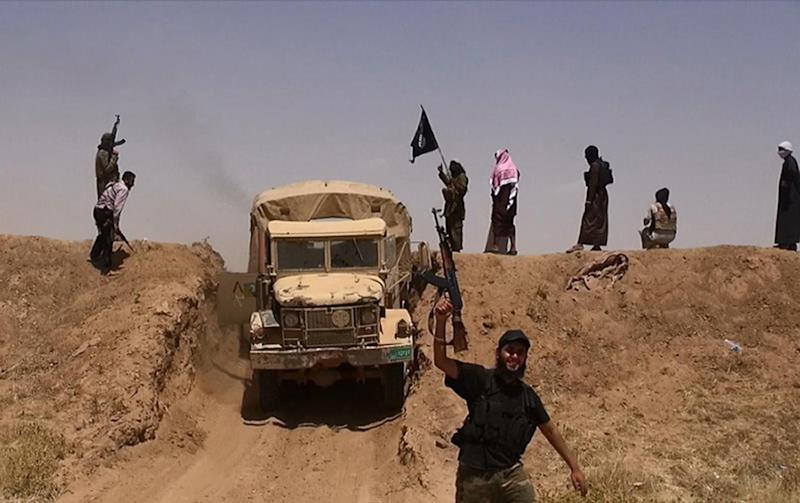 Militants of the jihadist group Islamic State drive across the border between Syria and Iraq in June 2014 (AFP Photo/)