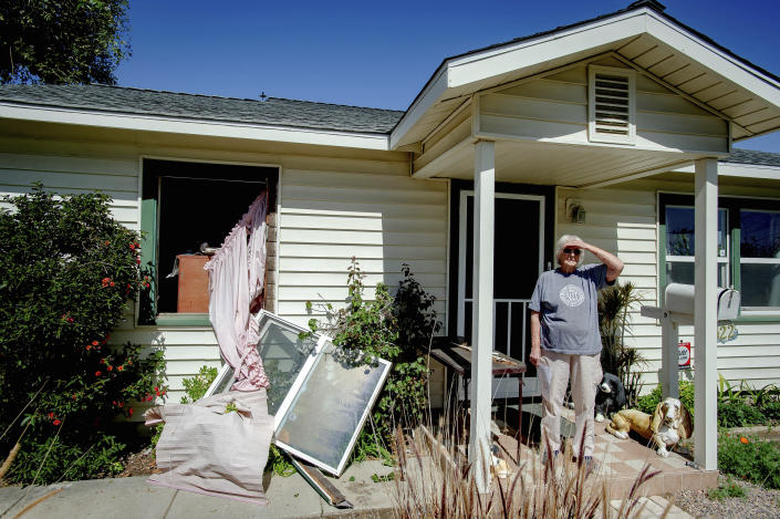 Van Vant stands in front of her home damaged home after a nearby fireworks stash exploded in Ontario, Calif., Tuesday, March 16, 2021. (Watchara Phomicinda/The Orange County Register via AP)