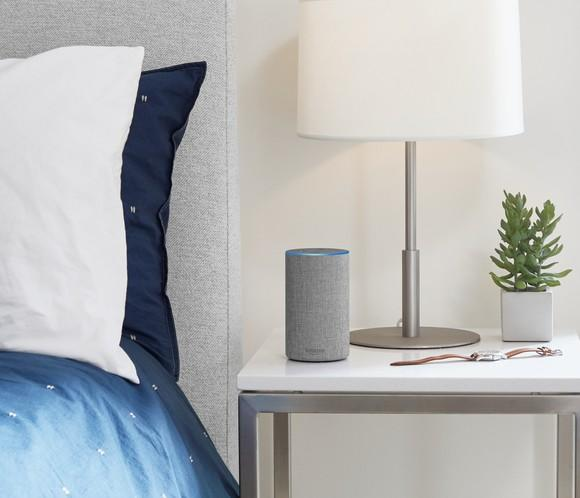 A gray Amazon Echo smart speaker on a nightstand next to a bed.