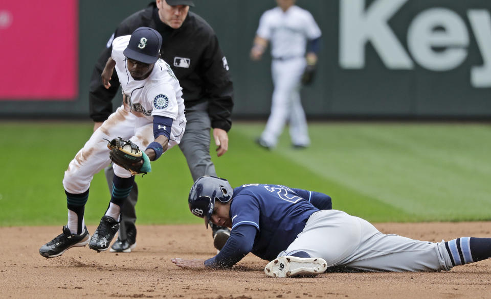 Tampa Bay Rays' Avisail Garcia, right, is safe diving back to second base as Seattle Mariners second baseman Dee Gordon, left, fields a pickoff-attempt during the seventh inning of a baseball game, Sunday, Aug. 11, 2019, in Seattle. (AP Photo/Ted S. Warren)