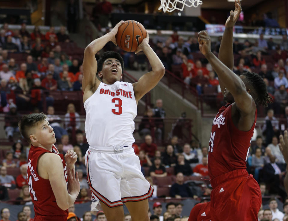 Ohio State's D.J. Carton, center, shoots between Nebraska's Thorir Thorbjarnarson, left, and Yvan Ouedraogo during the second half of an NCAA college basketball game Tuesday, Jan. 14, 2020, in Columbus, Ohio. Ohio State defeated Nebraska 80-68. (AP Photo/Jay LaPrete)