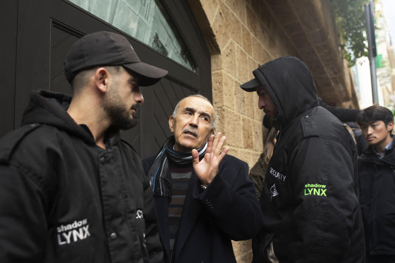 Private security guards flank a man who identified himself as a family doctor speaks to journalists as he enters the home of former Nissan Chairman Carlos Ghosn in Beirut, Lebanon, Thursday, Jan. 2, 2020. Turkish authorities have detained seven people as part of an investigation into how Ghosn, who skipped bail in Japan, was able to flee to Lebanon via Istanbul, Turkish media reported Thursday. (AP Photo/Maya Alleruzzo)