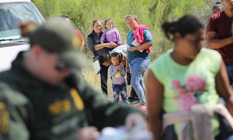 Central American asylum seekers wait as US border patrol agents take them into custody on 12 June 2018 near McAllen, Texas.