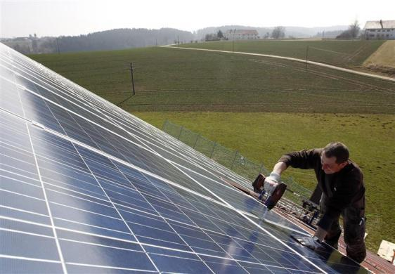 A worker mounts 320 square meters of solar panels on the roof of a farmstead barn in Binsham near Landshut March 21, 2012. German government plans cuts in the solar funding.