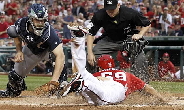 Washington Nationals' Jose Lobaton slides safely past the tag attempt by Atlanta Braves catcher Evan Gattis during the third inning of a baseball game at Nationals Park on Saturday, June 21, 2014, in Washington. (AP Photo/Alex Brandon)