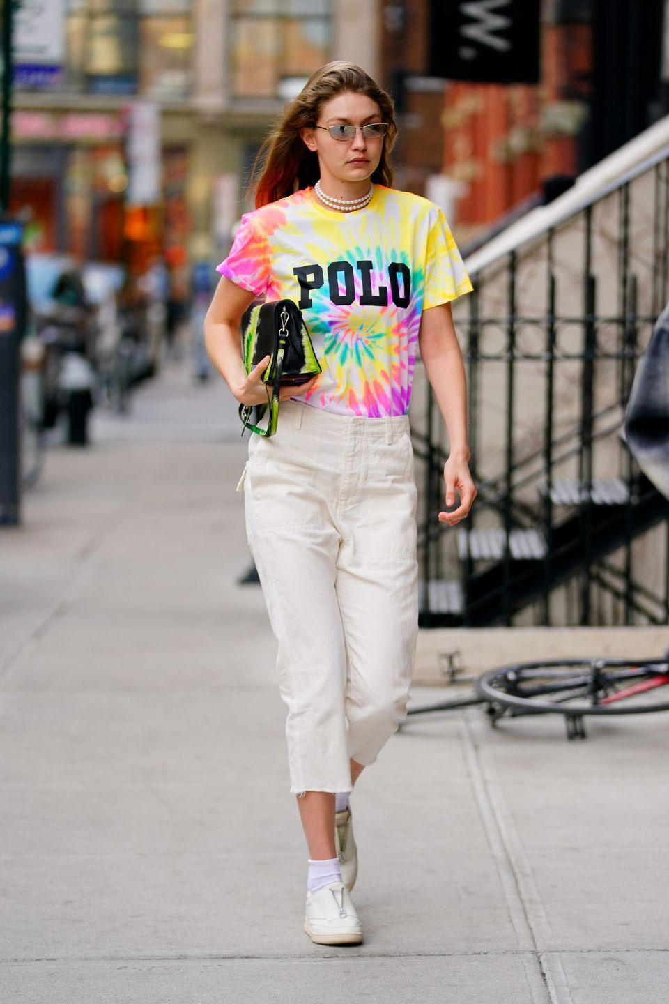<p>In a multicolor tie-dyed t-shirt, cropped creme pants, white sneakers, sunglasses, multi-stand pearl necklace, and a black handbag. </p>