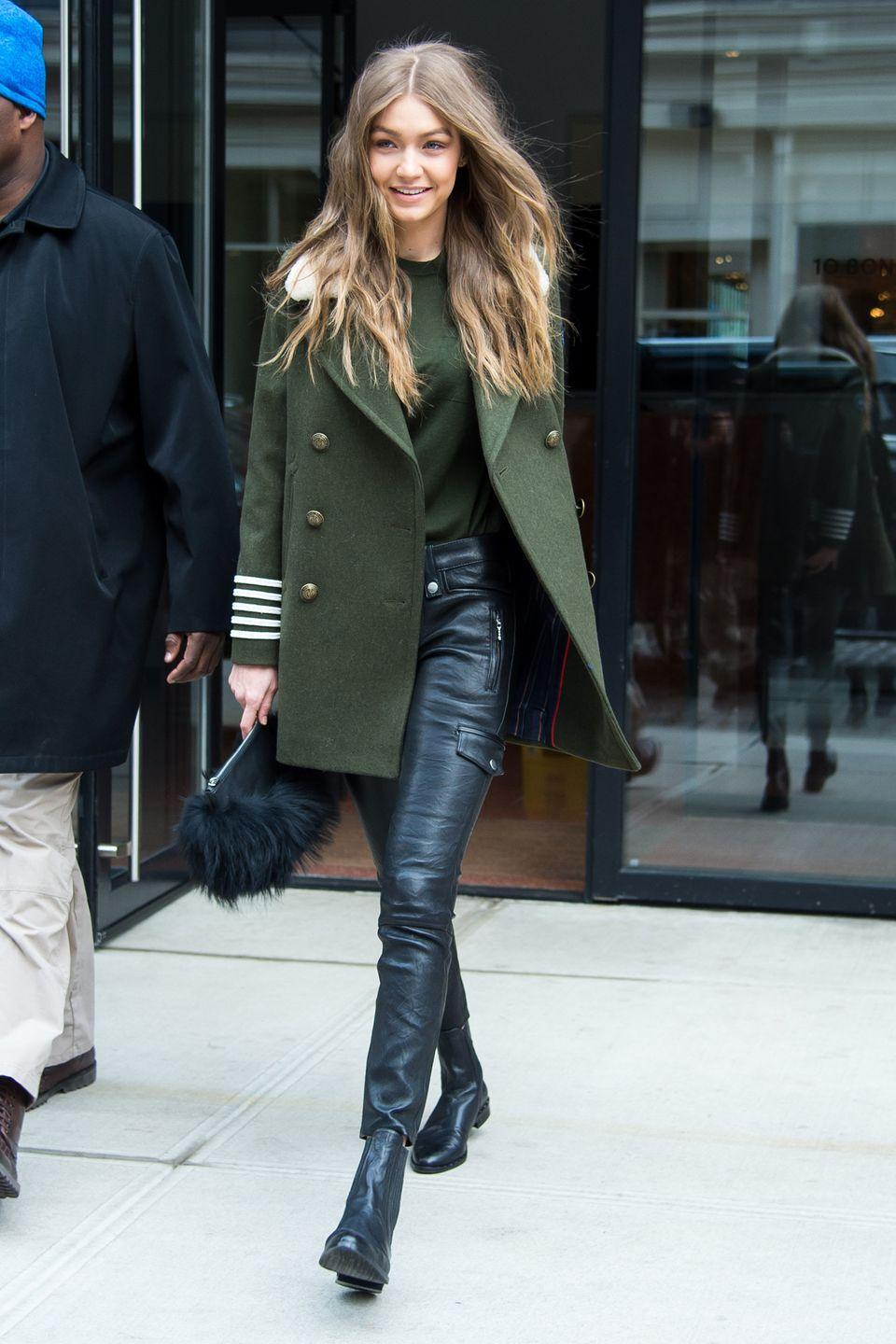 <p>While out in NYC, Hadid wore an olive green coat and sweater with FRAME black leather pants and ankle boots, and a furry black clutch. </p>