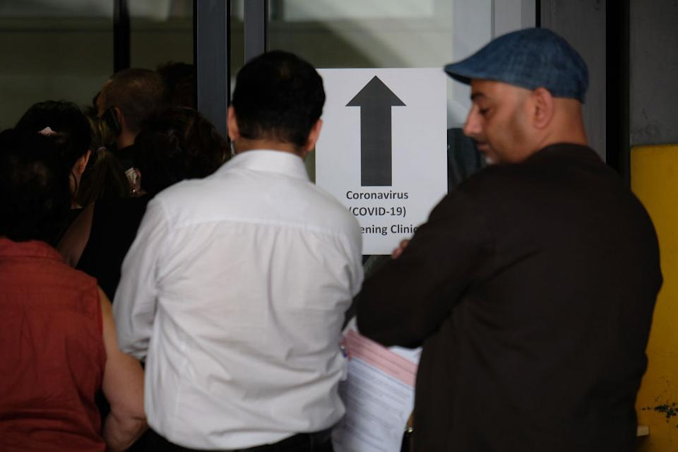 People wait in line to be screened for COVID-19 outside the Royal Melbourne Hospital.