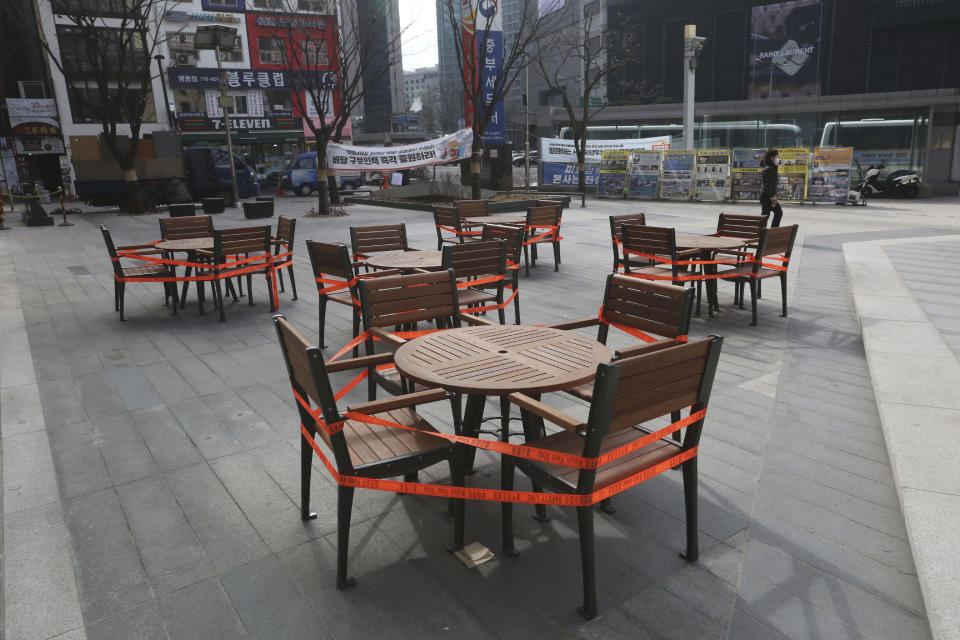 Tables and chairs are taped for social distancing along a shopping street in Seoul, South Korea, Sunday, Jan. 31, 2021. (AP Photo/Ahn Young-joon)