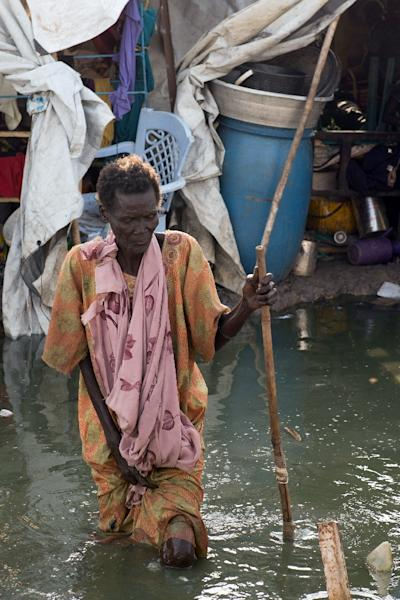 An elderly woman walks in dirty water littered by trash and infested by mosquitos at the United Nations Mission in South Sudan (UNMISS) site in Malakal, in South Sudan's northeastern Upper Nile State, on May 30, 2014 (AFP Photo/Charles Atiki Lomodong)