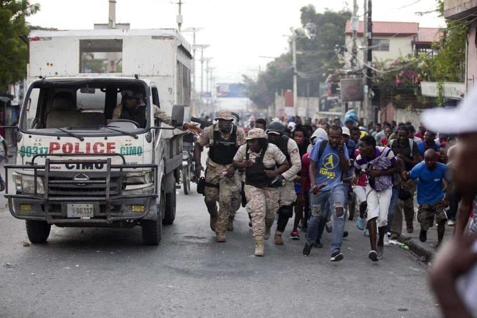 Police officers and protesters take cover behind a police truck as shots ring out during a protest to demand the resignation of Haiti's president Jovenel Moise on the 216th anniversary of Battle of Vertieres in Port-au-Prince, Haiti, Monday, Nov. 18, 2019. At least four people were shot and wounded during a small protest in Haiti's capital after a speech by embattled President Jovenel Moise. A local journalist, a police officer and two protesters were rushed away with apparent bullet wounds. (AP Photo/Dieu Nalio Chery)
