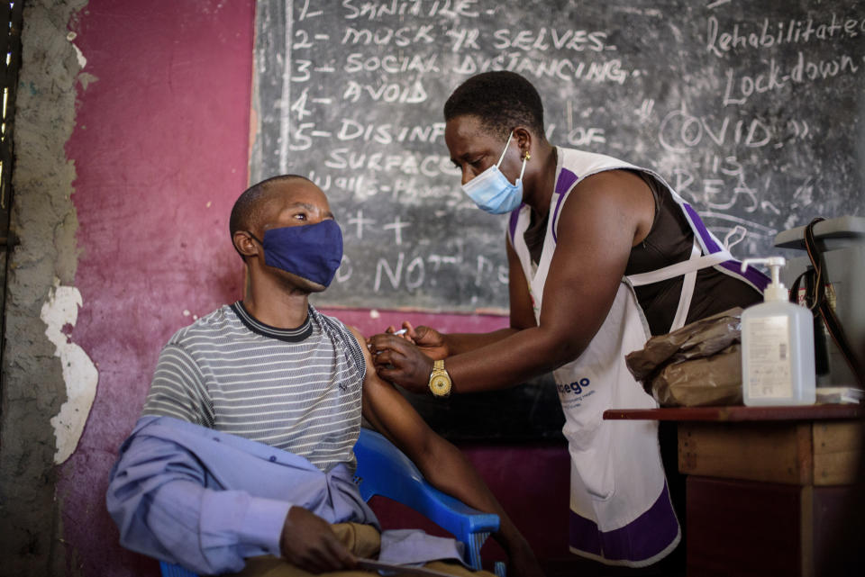 A nurse administers a coronavirus vaccination at Kisenyi Health Center in downtown Kampala, Uganda Wednesday, Sept. 8, 2021. Uganda is accelerating its vaccination drive in order to administer 128,000 doses that recently arrived and expire at the end of September. (AP Photo/Nicholas Bamulanzeki)