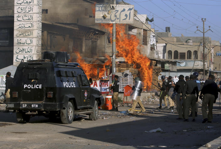 Police officers arrive to confront angry supporters of Tehreek-e-Labiak Pakistan, a radical Islamist political party, who set fires during protests following the arrest of their party leader Saad Rizvi, in Karachi, Pakistan, Tuesday, April 13, 2021. (AP Photo/Fareed Khan)