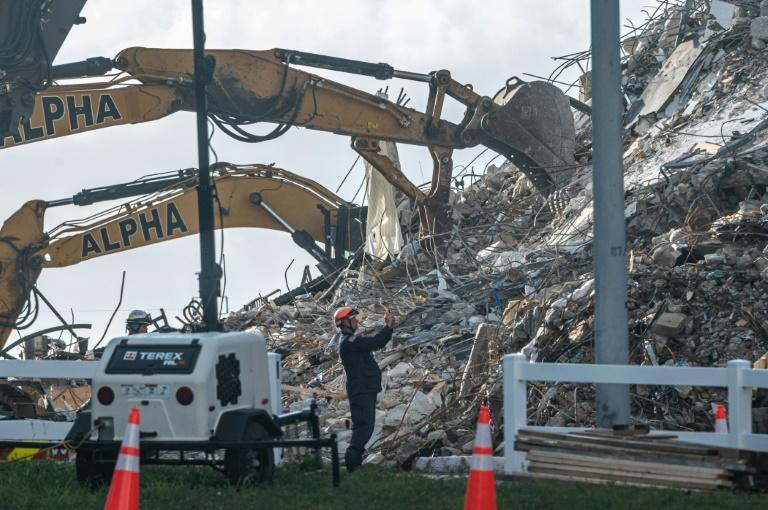 Members of the South Florida Urban Search and Rescue team look for possible survivors in the partially collapsed 12-story Champlain Towers South condo building on June 27, 2021 in Surfside, Florida