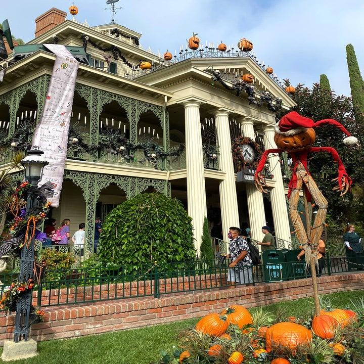 Outside the Haunted mansion dressed up with pumpkins, candles, a scarecrow wearing a santa suit, and a long list of gifts from the nightmare before christmas