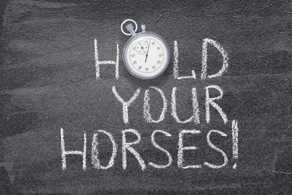 """Hold your horses"" written on chalkboard with a vintage stopwatch used instead of O."