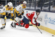 Columbus Blue Jackets' Jack Roslovic, right, tries to clear the puck as Nashville Predators' Roman Josi, left, and Matt Benning defends during the second period of an NHL hockey game Saturday, Feb. 20, 2021, in Columbus, Ohio. (AP Photo/Jay LaPrete)