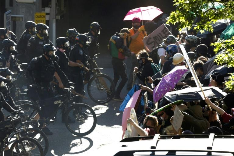Police in Seattle faced off against protestors, some holding umbrellas against falling pellets of pepper spray (AFP Photo/Jason Redmond)