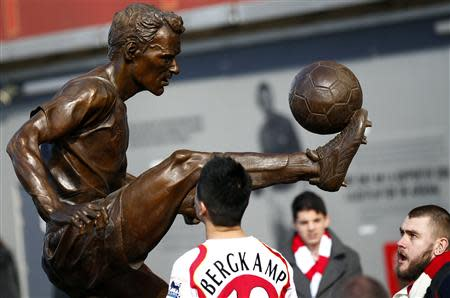 Arsenal fans look at a statue of former striker Dennis Bergkamp after it was unveiled before their English Premier League soccer match against Sunderland in London