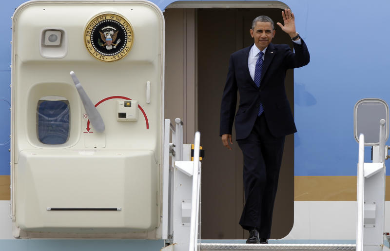 President Barack Obama waves as he arrives at Miami International Airport in Miami, Wednesday, June 12, 2013. The president is attending a fundraiser in Miami Beach Wednesday night. (AP Photo/Lynne Sladky)