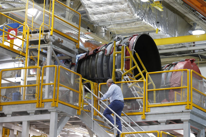 An employee walks up to two of the four rocket engines of NASA's Space Launch System (SLS) as the Artemis 1 rocket core stage is assembled at the NASA Michoud Assembly Center in New Orleans, Monday, Dec. 9, 2019. (AP Photo/Gerald Herbert)