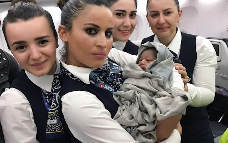 Flight crew with the newborn baby - Turkish Airlines / SWNS.com