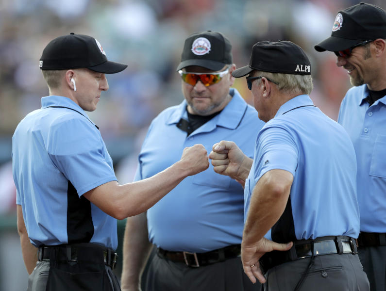 FILE - In this July 10, 2019, file photo, home plate umpire Brian deBrauwere, left, huddles with officials while wearing an earpiece connected to a ball and strikes calling system before the Atlantic League All-Star minor league baseball game in York, Pa. DeBrauwere wore the earpiece connected to an iPhone in his ball bag which relayed ball and strike calls upon receiving it from a TrackMan computer system that uses Doppler radar. The independent Atlantic League became the first American professional baseball league to let the computer call balls and strikes during the all star game. Umpires agreed to cooperate with Major League Baseball in the development and testing of an automated ball-strike system as part of a five-year labor contract announced Saturday, Dec. 21, two people familiar with the deal told The Associated Press. The Major League Baseball Umpires Association also agreed to cooperate and assist if Commissioner Rob Manfred decides to utilize the system at the major league level. The people spoke on condition of anonymity because those details of the deal, which is subject to ratification by both sides, had not been announced. (AP Photo/Julio Cortez)