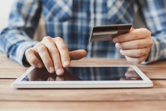 Man puts credit card information in ecommerce website with a tablet computer.