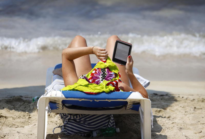 MUJER LEE EN LA PLAYA EN UN EBOOK FOTO: CLARA MARGAIS /GETTY IMAGES