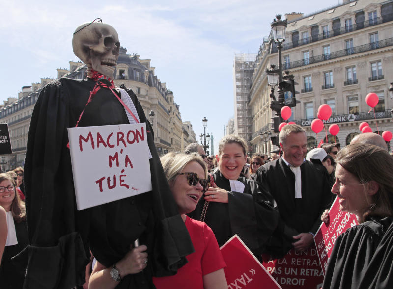 """A lawyer holds a effigy with a scull represending a dead lawyer march during a protest against the planned pension change in Paris, Monday, Sept. 16, 2019. French lawyers, doctors, nurses, pilots and others are taking to the streets of Paris to protest planned pension changes by French President Emmanuel Macron's government. Placard read, """"no to the pension tax"""". Placard reads, """"Macron wants my dead"""". (AP Photo/Michel Euler)"""